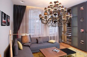 modern-small-apartment-living-room-grey-modular-sofa-square-wooden-coffee-table-innovative-diy-wooden-reading-lamp-grey-storage-wall-panel-elegant-ceiling-mount-iron-chandelier-pendan