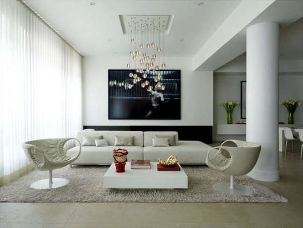 white couch and 2 modern chairs, white coffee table, white walls, black artwork, contemporary chandelier over table